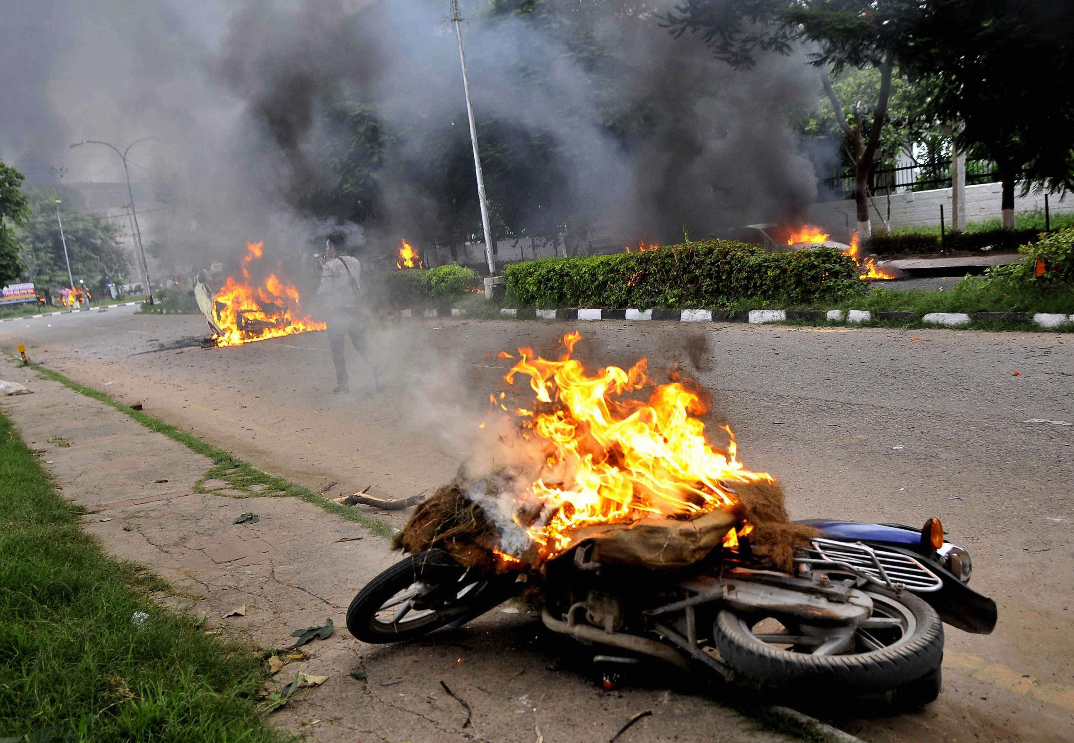 A motorcycle on fire in Panchkula, Haryana, which was at the centre of the violence. (Credit: PTI)