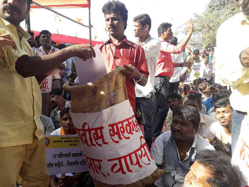 "Sanitation workers threw copies of a government resolution in a trash bag as part of a protest they called ""GR wapsi"". (Photo credit: Aarefa Johari)."