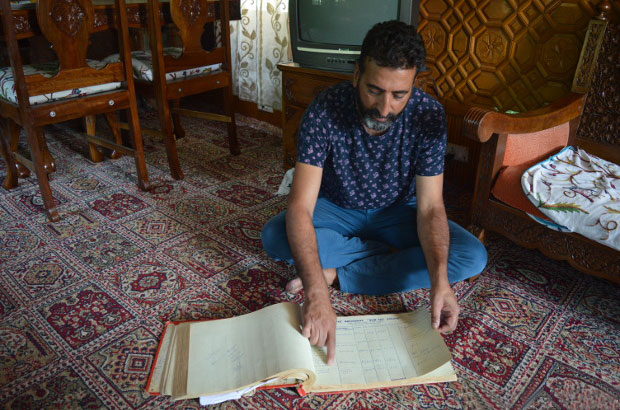 Tariq Ahmad Patloo showing the entries of foreign guests during 1980s from an old log book of his house-boat New Sea Palace. Photo credit: Athar Parvaiz/IndiaSpend.com