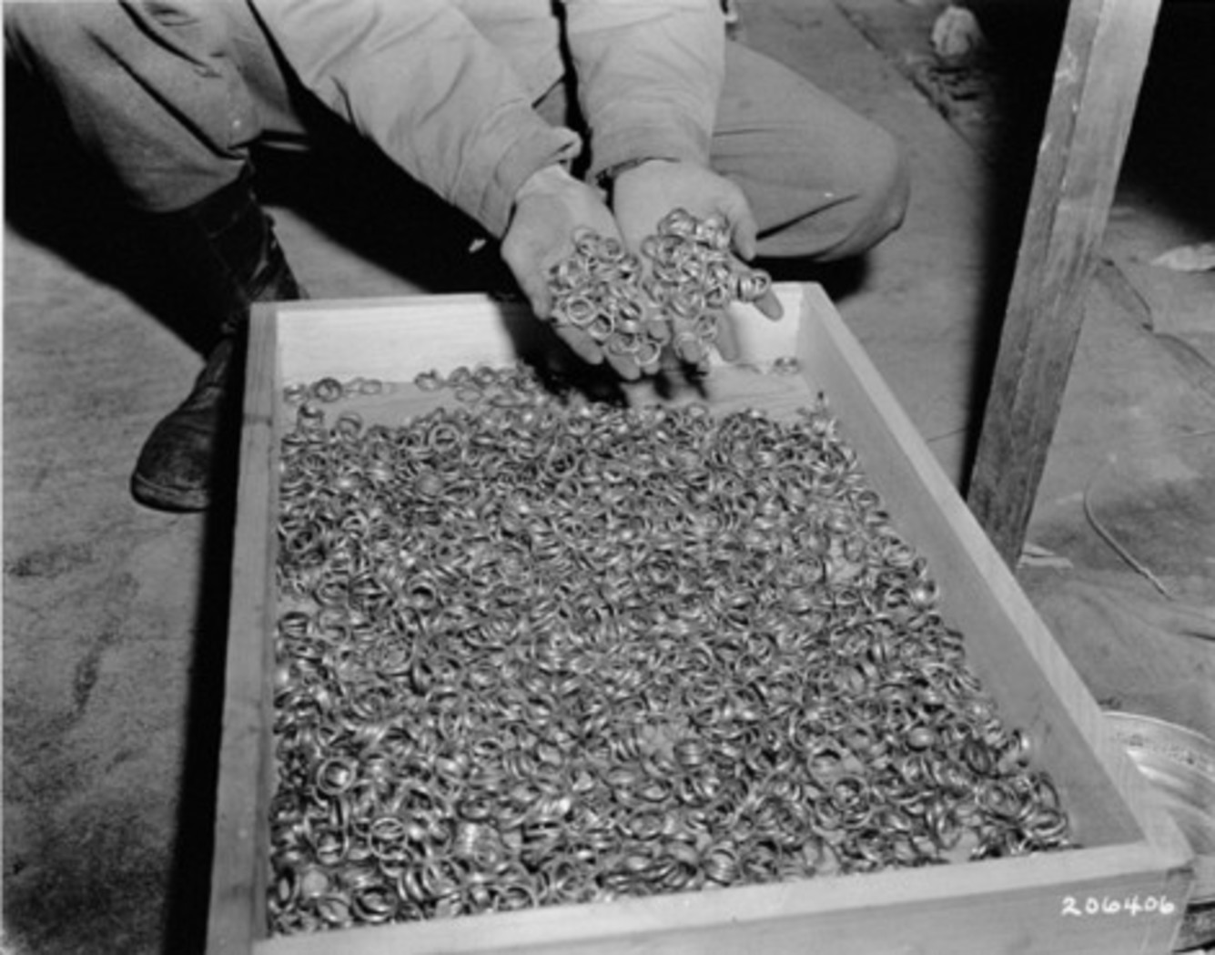 In this May 1945 image, a U.S. soldier dips his hands into a crate full of rings confiscated from prisoners in Buchenwald.  National Archives and Records Administration