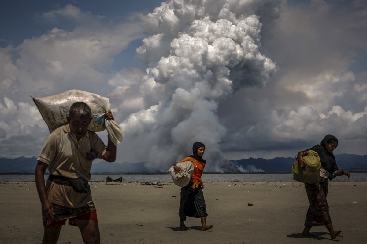 Smoke is seen on the Myanmar border as Rohingya refugees walk on the shore after crossing the Bangladesh-Myanmar border by boat through the Bay of Bengal, in Shah Porir Dwip, Bangladesh, in September 2017. Photo: Danish Siddiqui/Reuters