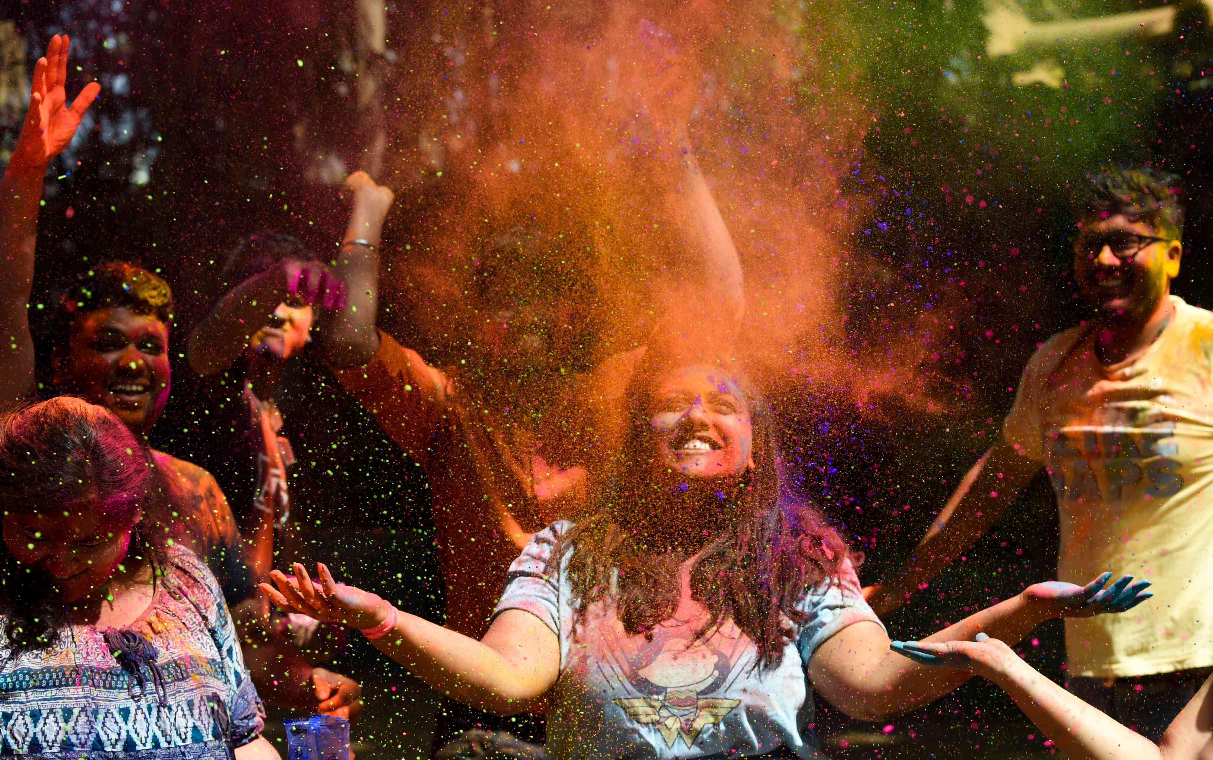 Revellers throw colours during Holi celebrations in Mumbai on Thursday. | Credit: AFP