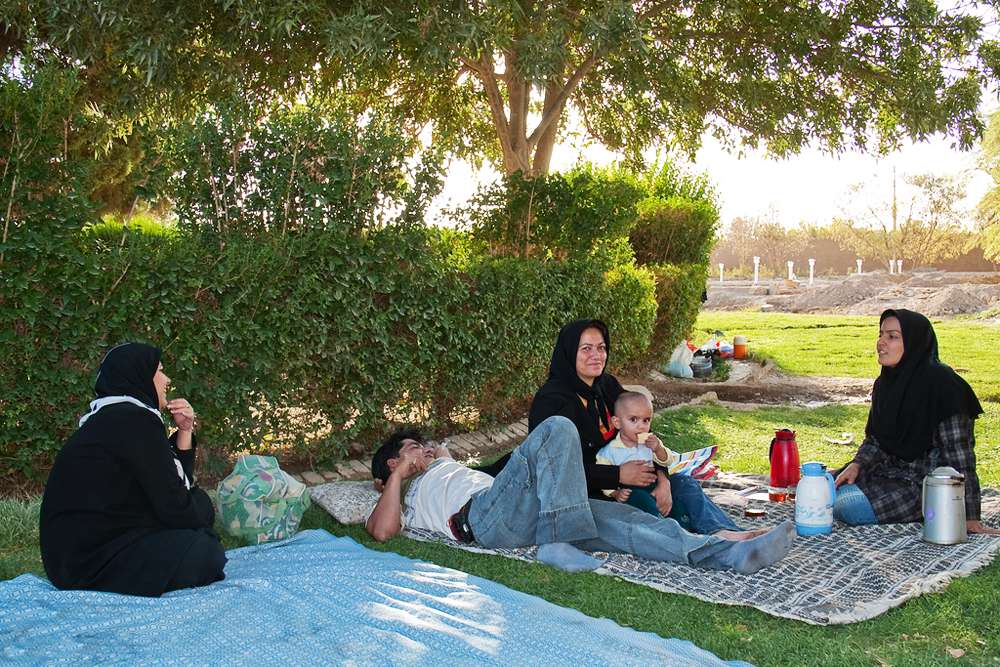 A family enjoys the Friday holiday in park near the Azadi Square in Tehran. Tehran has many parks, and spaces of recreational activities. In Iran, people like to spend their weekends and evenings holding family picnics in these parks.