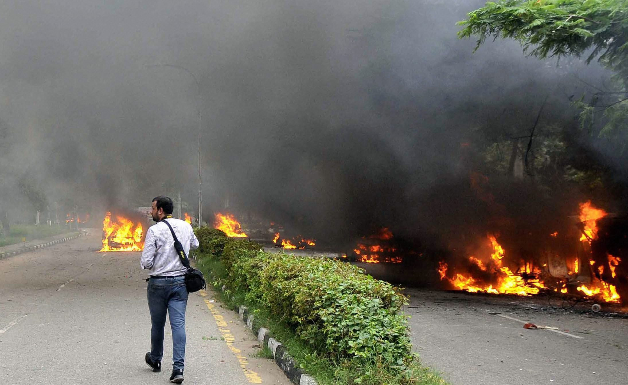 A photojournalist walks past burning vehilces in Panchkula, which was hit the worst by the riots. (Credit: PTI)
