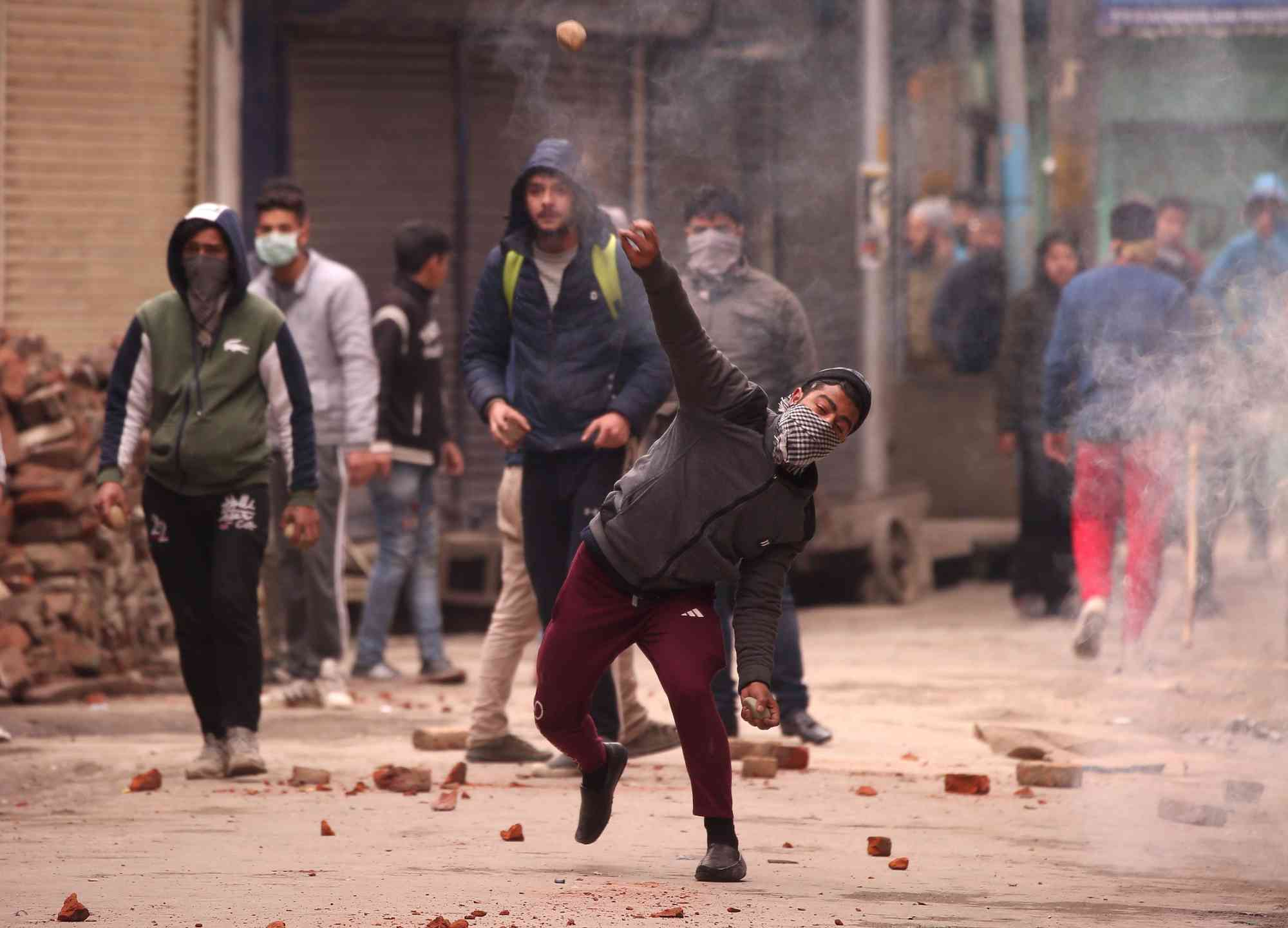 A demonstrator in Srinagar throws a piece of brick towards the police (unseen) during a protest after the National Investigation Agency carried out a raid at the residence of Yasin Malik, chairman of the separatist Jammu Kashmir Liberation Front, on February 26, 2019. (Photo credit: Danish Ismail/Reuters)