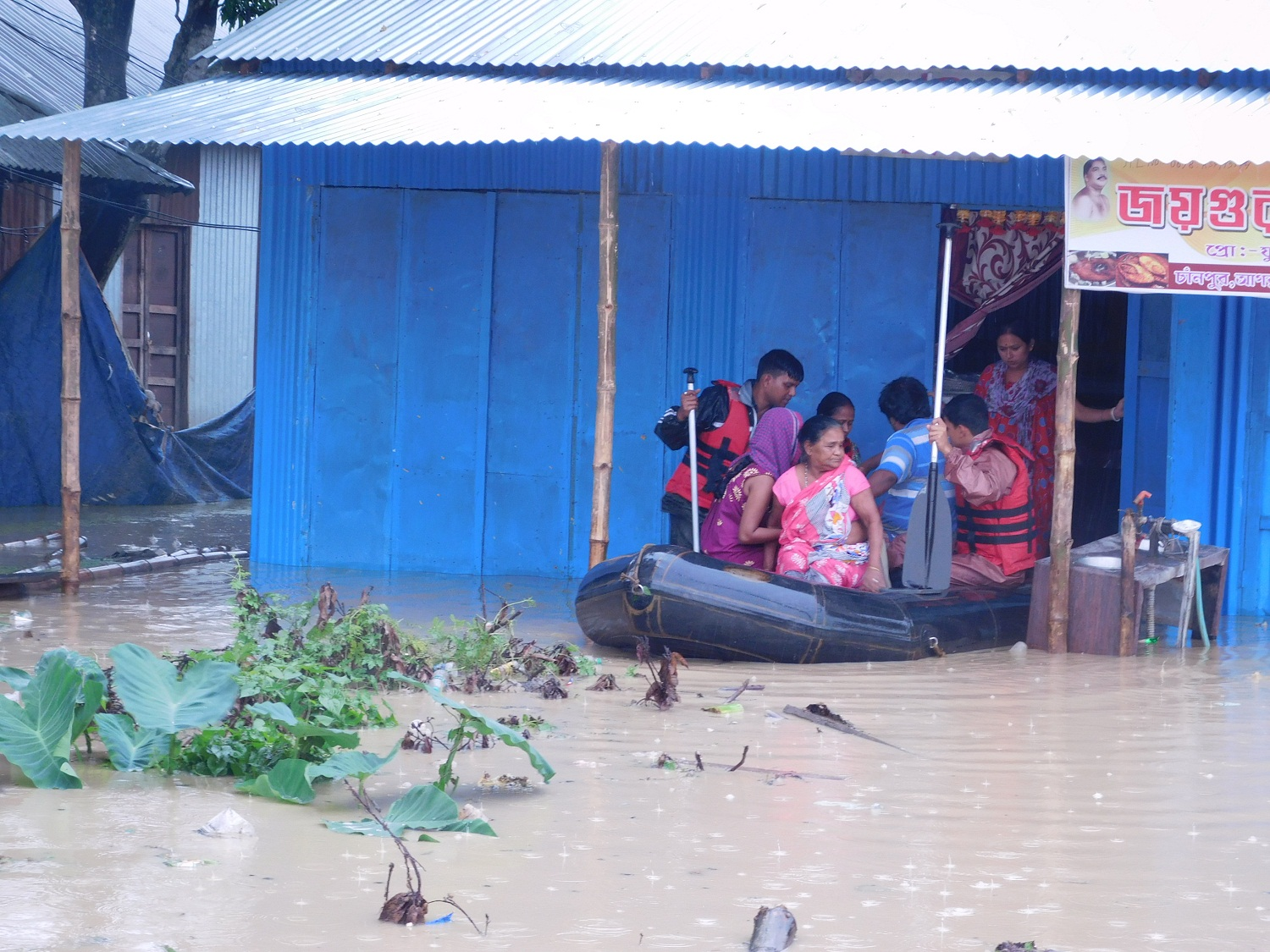 People using boats to navigate in a flooded suburb near Agartala