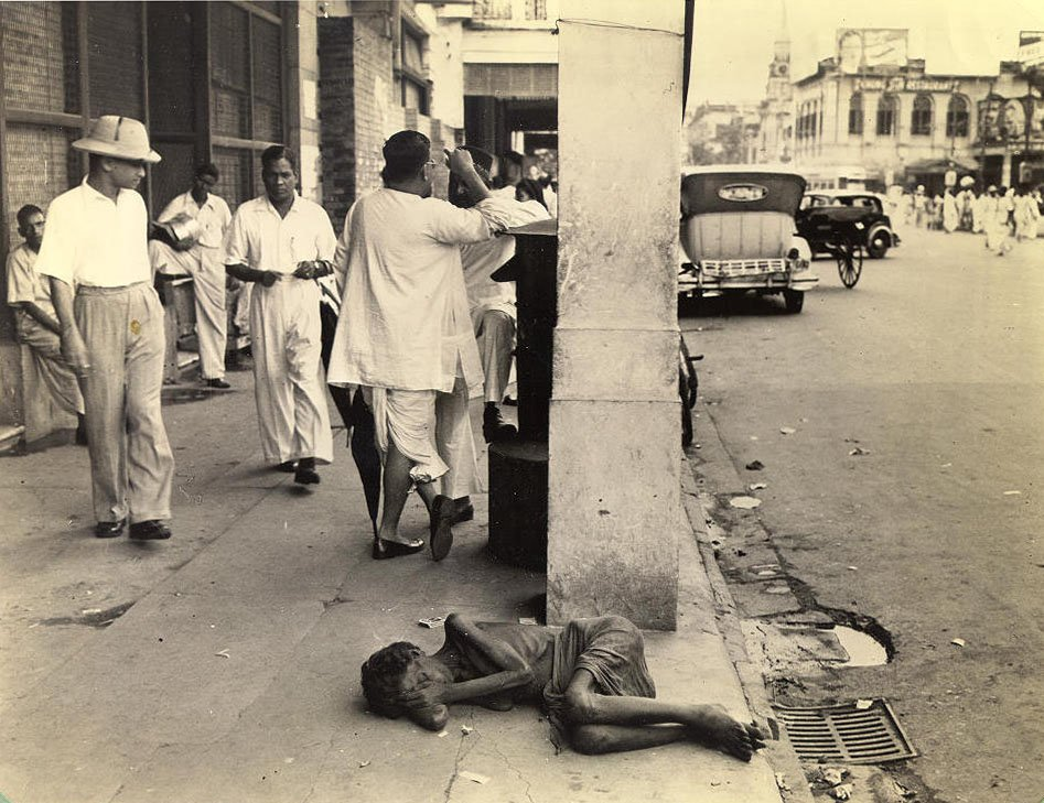 """The indifference of the passerby on this downtown Calcutta street to the plight of the dying woman in the foreground is considered commonplace. During the famine of 1943, cases like this were to be seen in most every block, and though less frequent now, the hardened public reaction seems to have endured."" Photo credit: Clyde Waddell/University of Pennsylvania/Wikimedia Commons [Public Domain]"