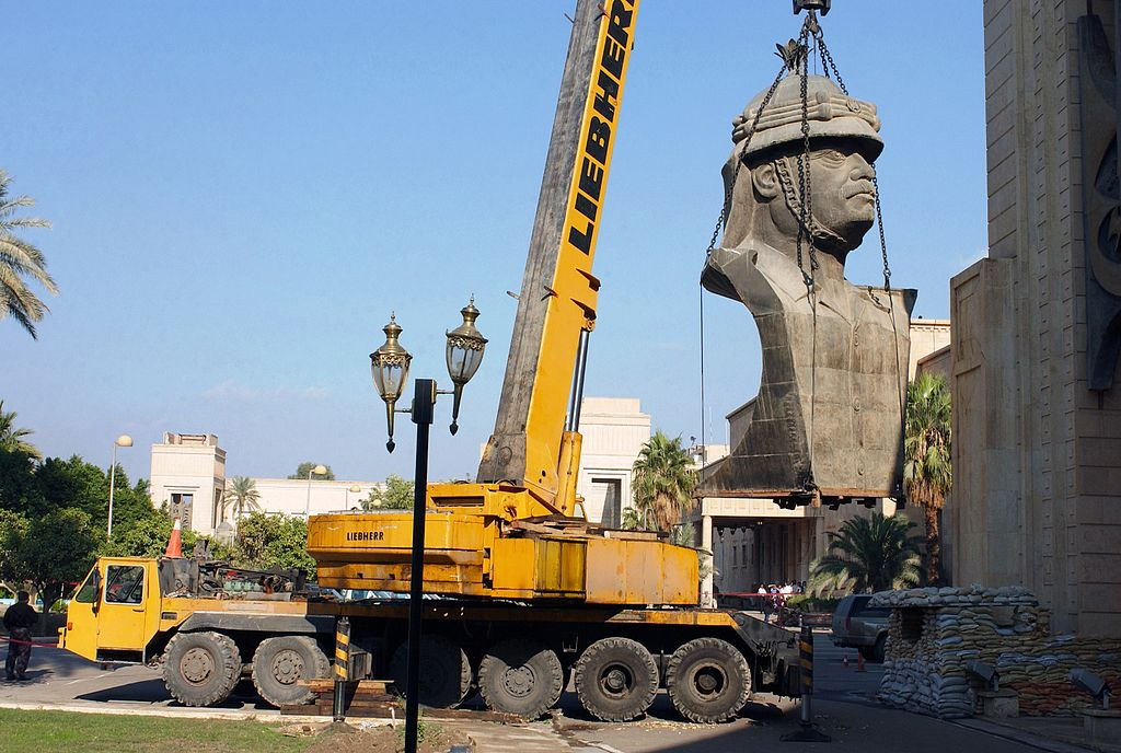 A crane removes the last large bust of Saddam Hussein from the top of the former Presidential Palace in Baghdad