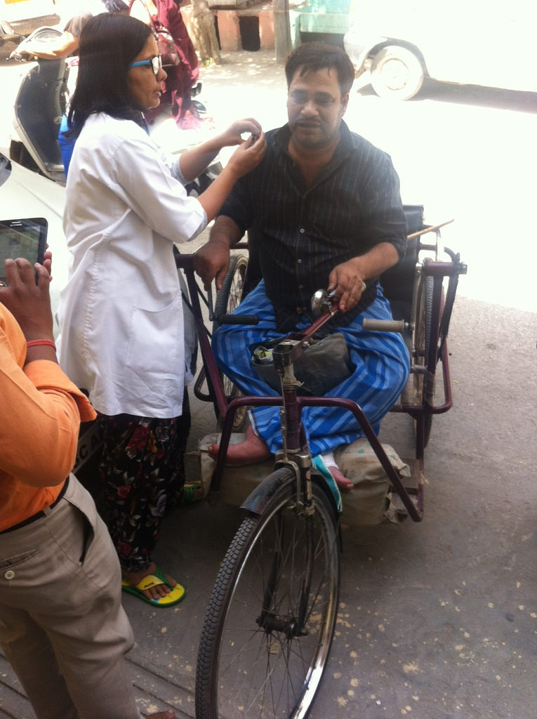 A doctor examines Munna Singh, a physically handicapped person, outside the Krishna Nagar mohalla clinic. (Photo: Menaka Rao)