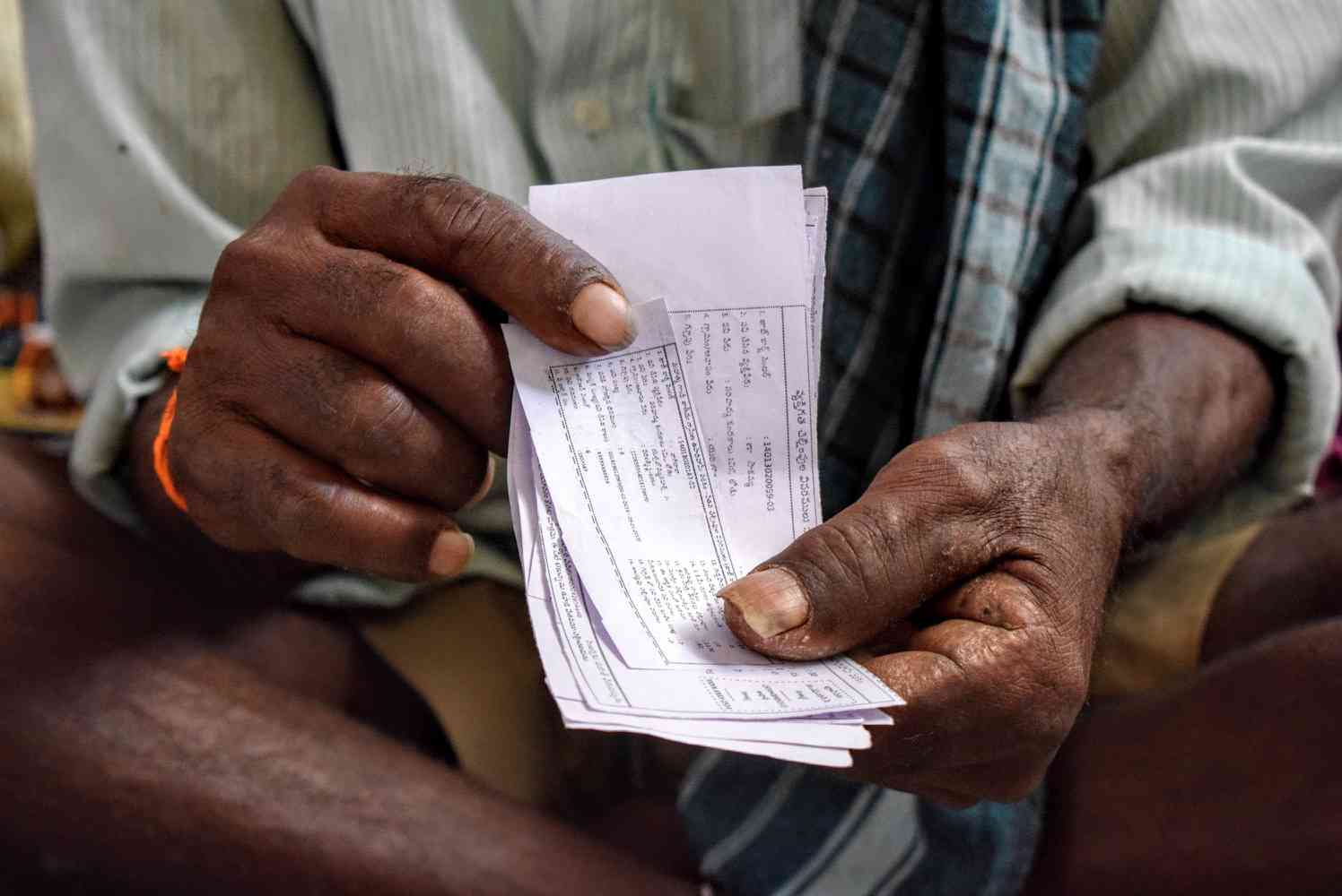 An old man clutches a bundle of paper slips showing the number of days he has worked under NREGA, work for which he has not been paid. Photo: Aruna Chandrasekhar