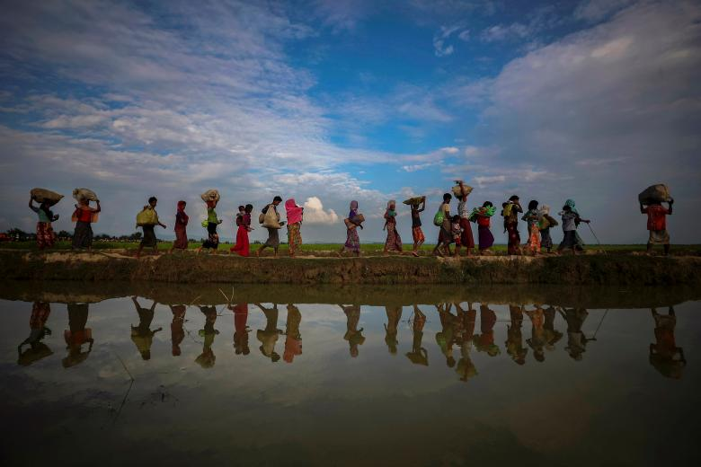 Rohingya refugees walk along an embankment after fleeing from Myanmar into Palang Khali, near Cox's Bazar, Bangladesh, on November 2, 2017. Photo: Hannah McKay/Reuters