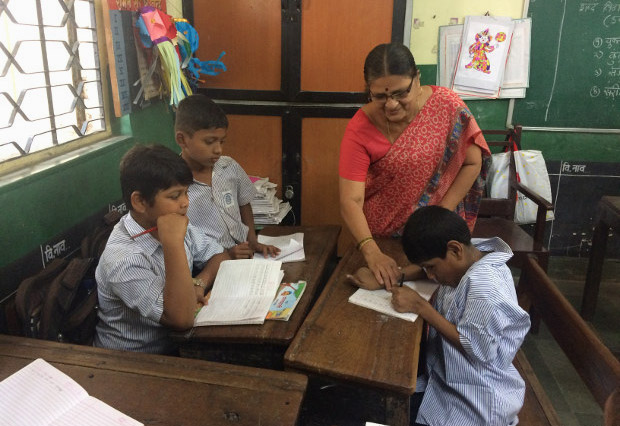 Javed Shaikh with his class teacher, Charulata Patil, at the Jagannath Bhatankar Municipal Corporation School in Parel, Mumbai. When IndiaSpend visited Javed in his school in November, he was writing alphabets in his notebook and would smile when Patil called to him. (Photo credit: Swagata Yadavar)