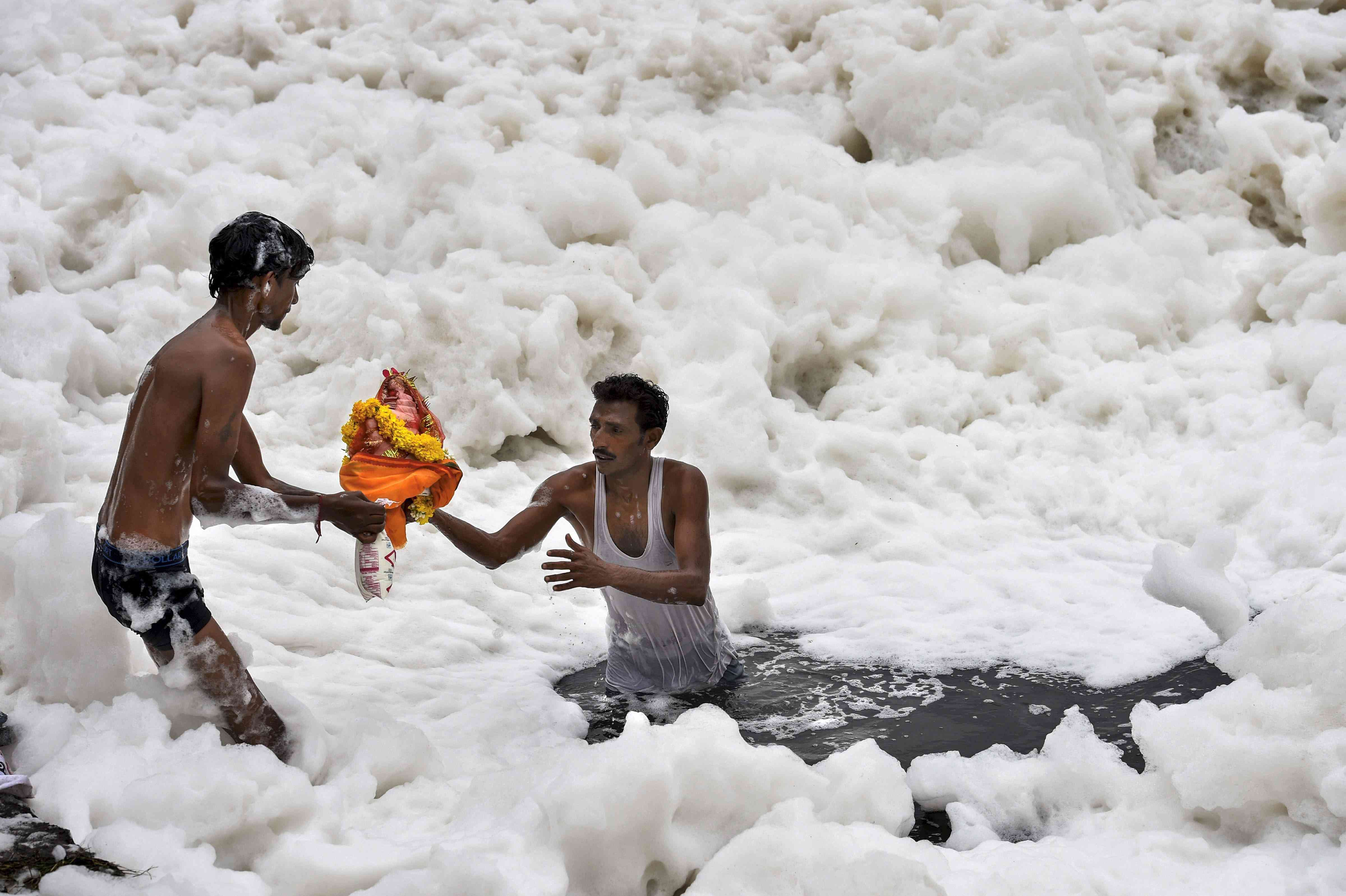 Devotees carry an idol of Ganesha to immerse it in Yamuna in Delhi on Sunday. (Credit: PTI)
