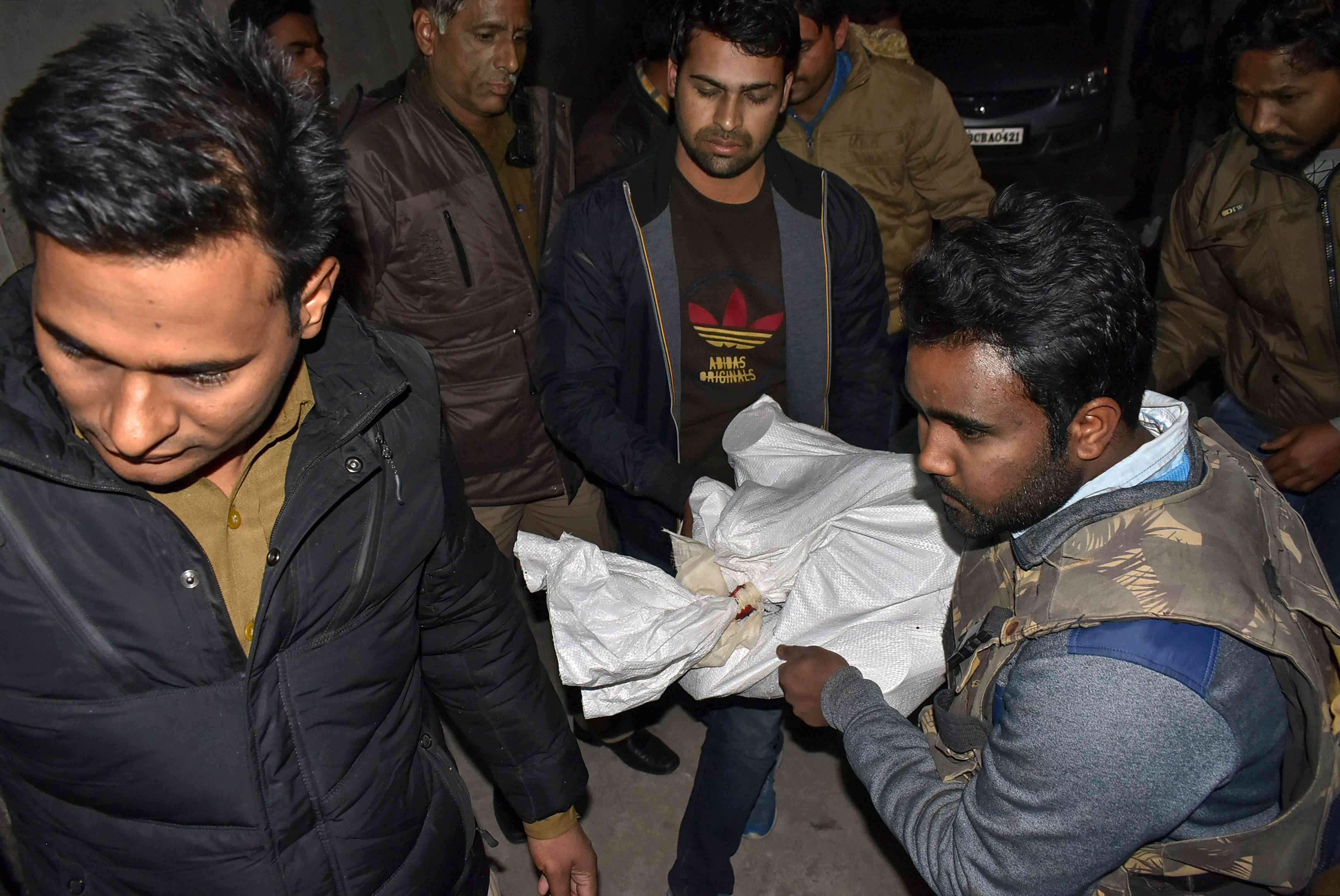 NIA officials carry away material seized during raids on Wednesday. Credit: PTI