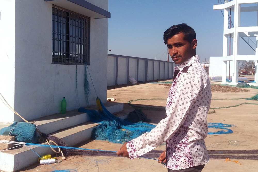 Elias Husain Moda repairing fishing nets at the Salaya bunder.