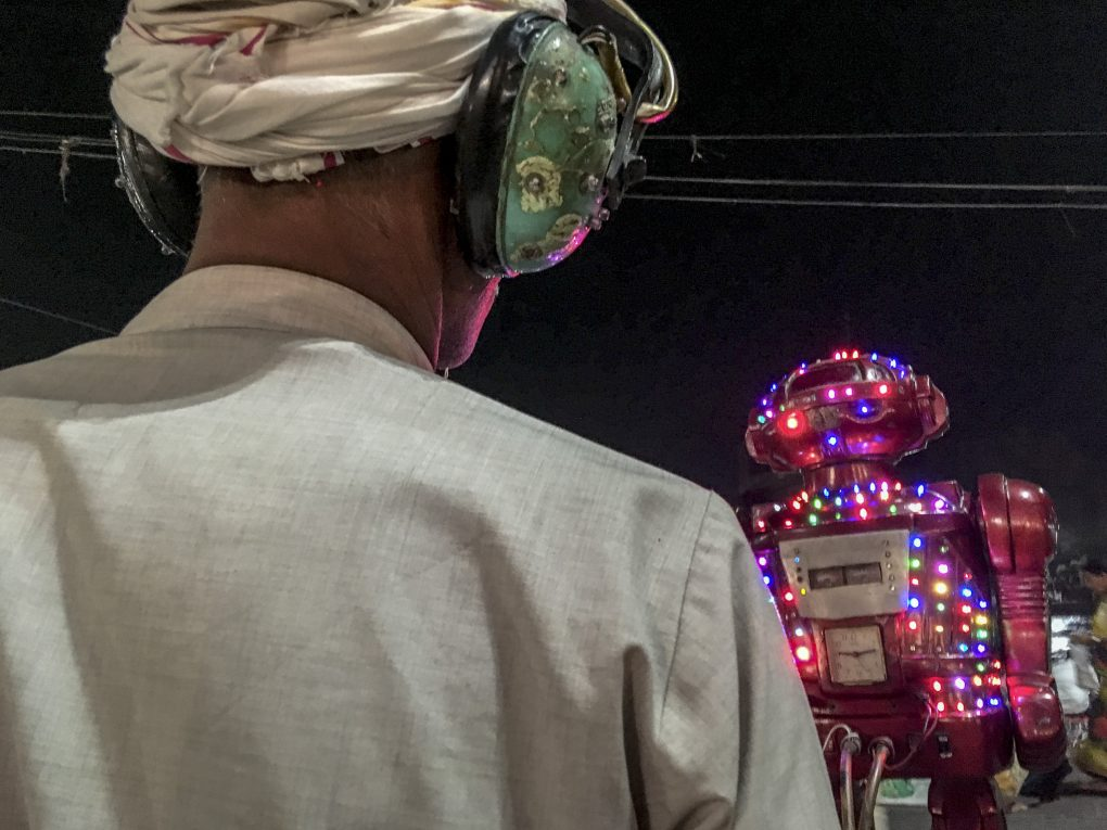 Man listening to what a robot has to predict for his future, a common sight at Indian fairs and festivals.