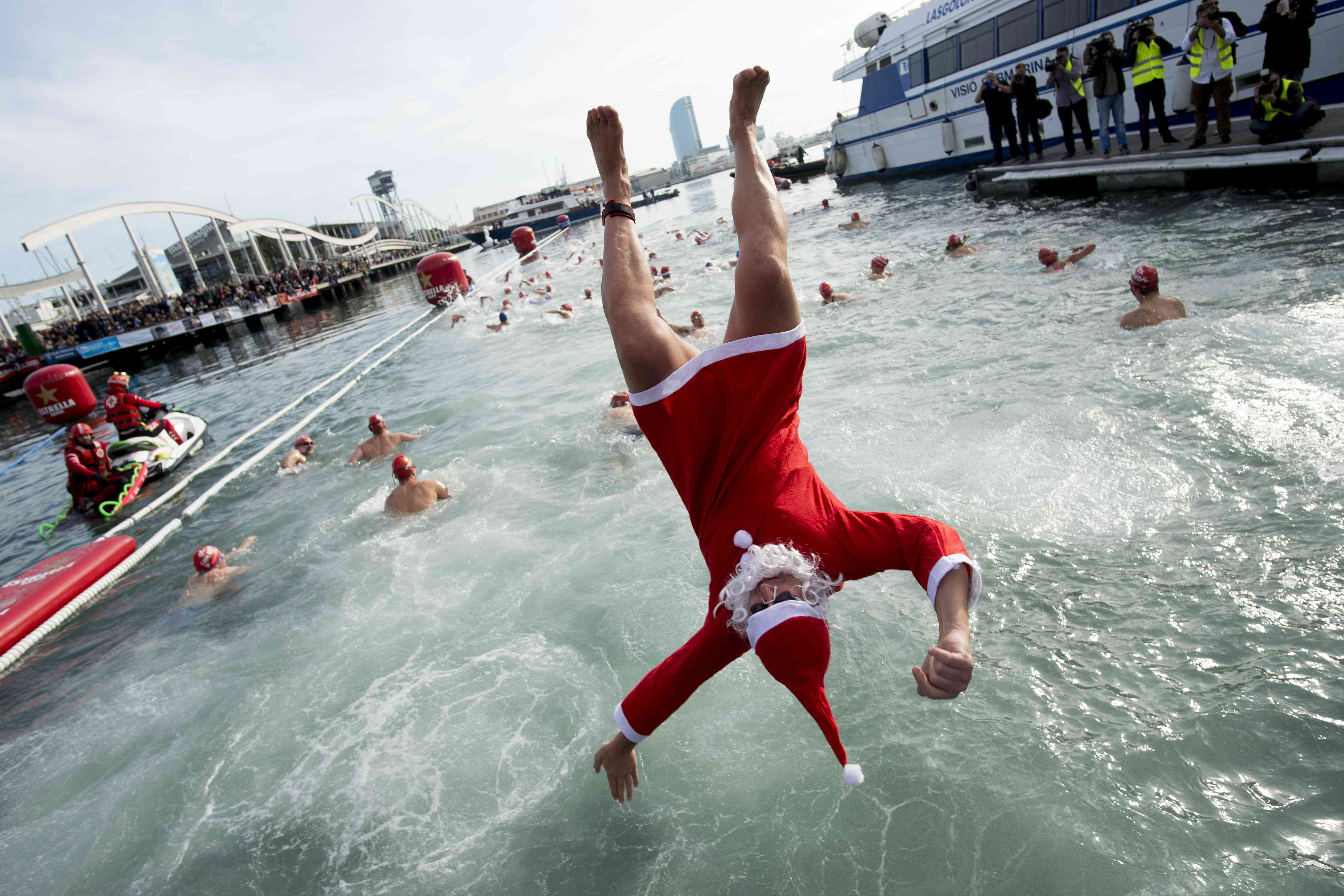 A participant in a Santa Claus costume jumps into the water during the 109th edition of the 'Copa Nadal' (Christmas Cup) swimming competition in Barcelona, Spain, on Tuesday. (Photo credit: Josep Lago/AFP)