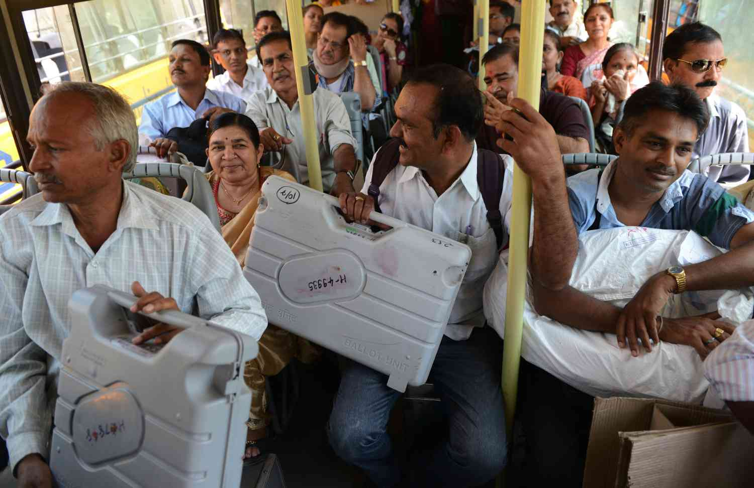 Election officials hold their Electronic Voting Machines as they sit in a bus on their way to various polling stations from a distribution centre in Ahmedabad on April 29, 2014. (Photo credit: AFP/Sam Panthaky).