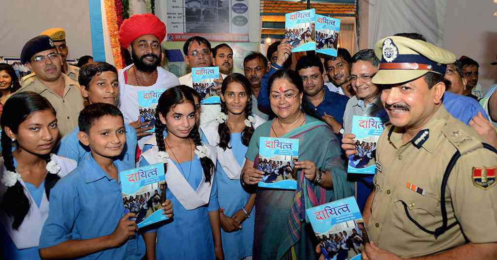 Chief minister Vasundhara Raje with school students. The book title is 'Dayitva' or 'Responsibilty'.