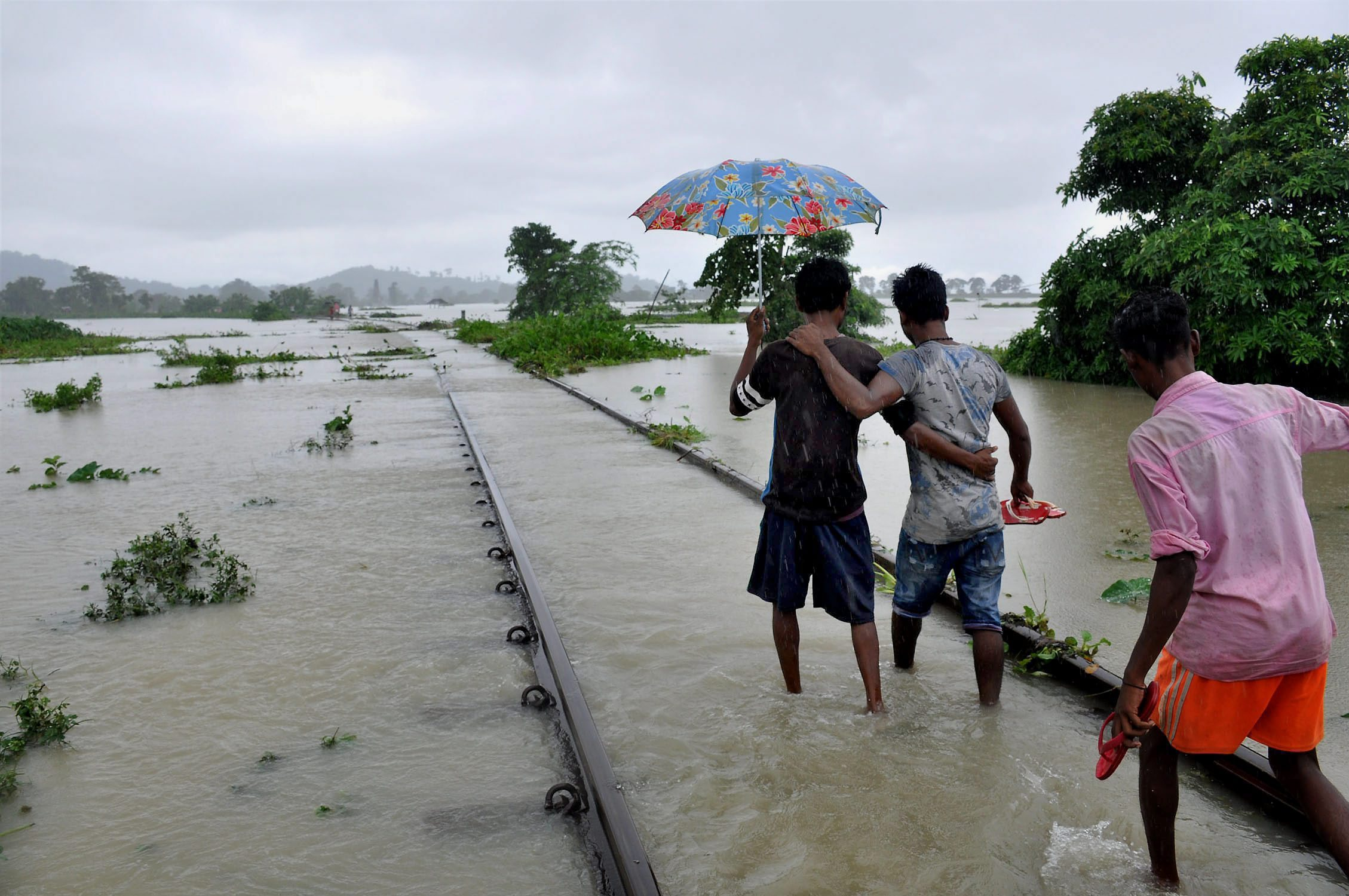 People walk in ankle-deep waters along a submerged railway track in Nagaon district in Assam. (Credit: PTI)