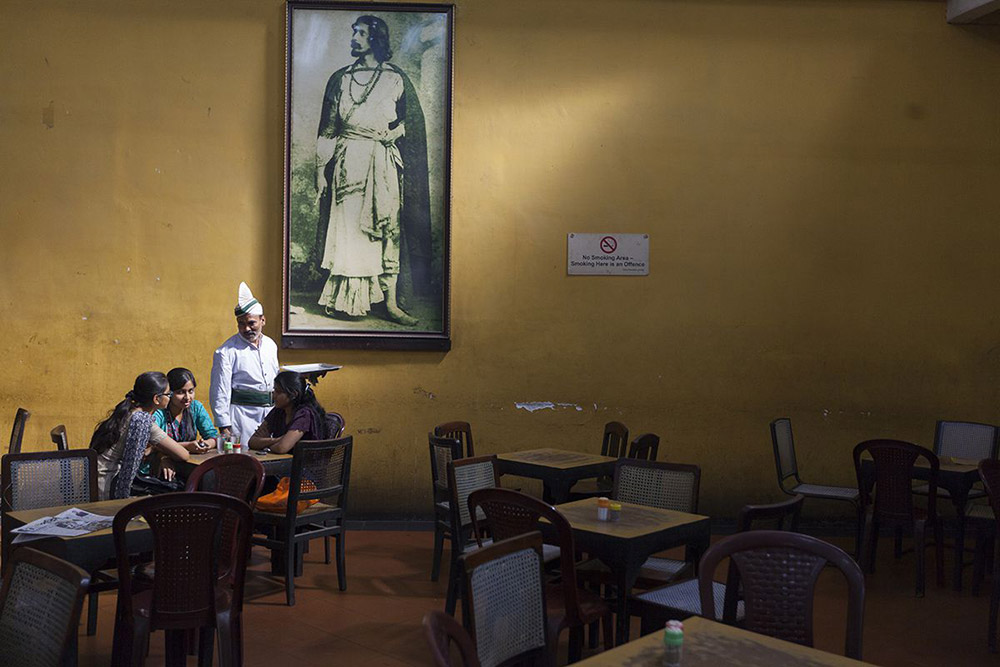 A waiter serves schoolgirls beneath a portrait of Rabindranath Tagore in the Indian Coffee House, Kolkata, India.  (© Stuart Freedman, Courtesy Tasveer)