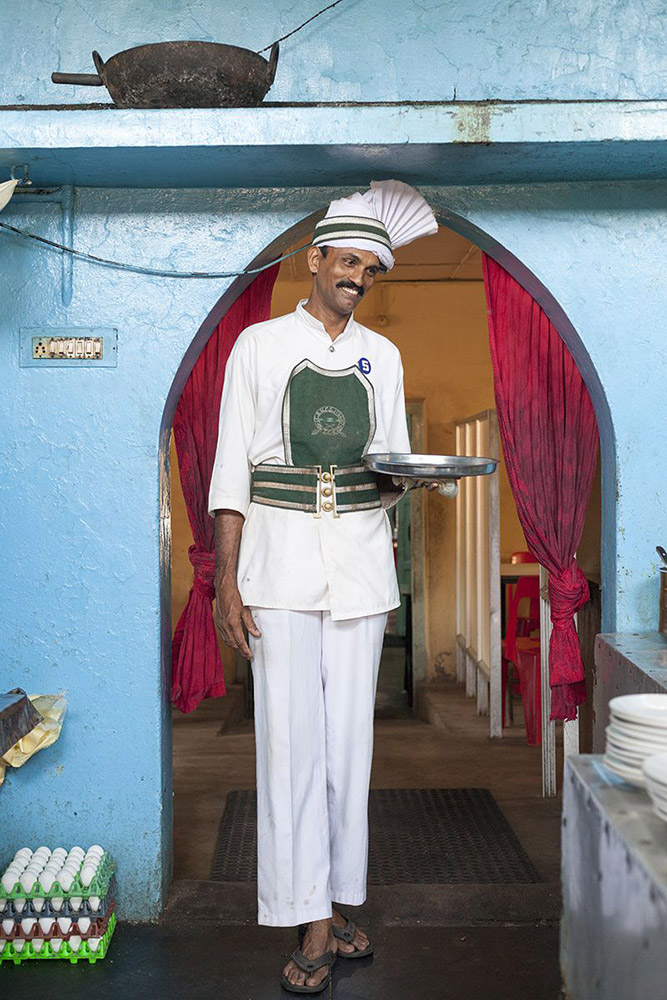 Sangaran, a waiter who has worked at the coffee shop for 17 years. The Indian Coffee House, Kollam, India.  (© Stuart Freedman, courtesy Tasveer)