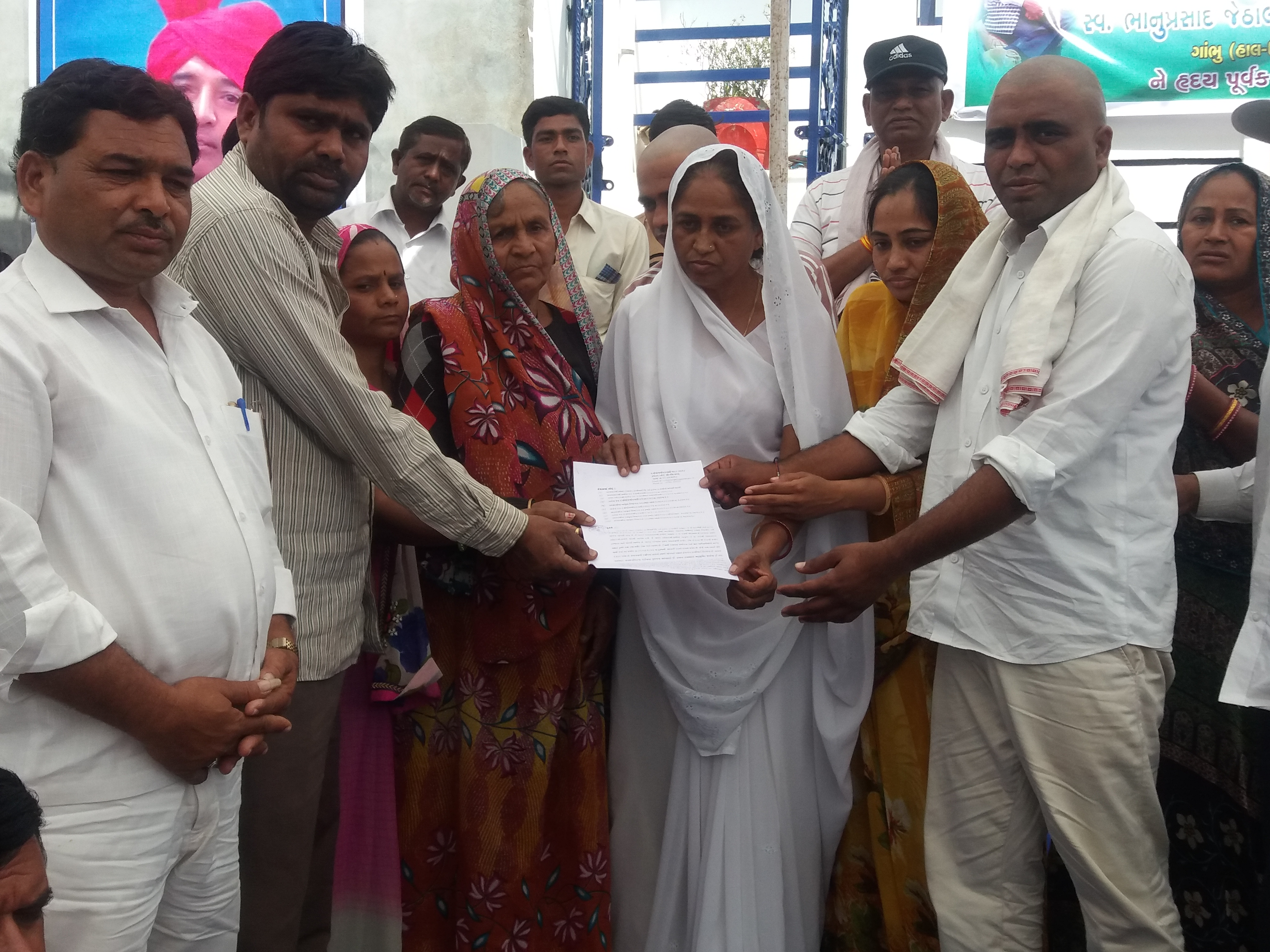 Government officials and Bhanubhai Vankar's widow hand over the land re-grant papers to Hemaben Vankar and Ramabhai Chamar at a condolence meet on February 20.