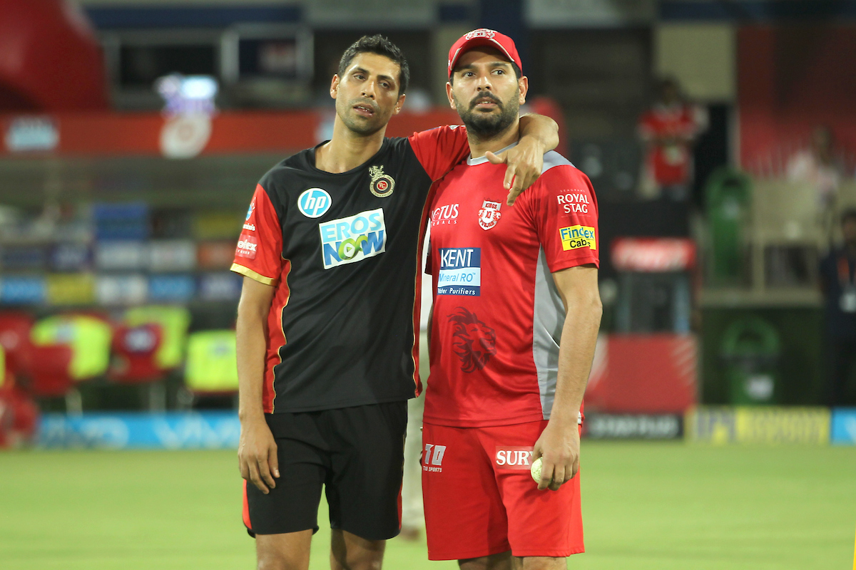 Former India team-mates Ashish Nehra (left) and Yuvraj Singh catch up ahead of start of play. Photo: Sportzpics.