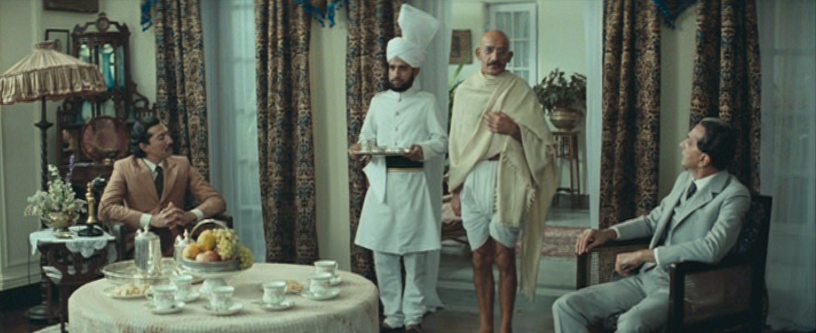 Mahatma Gandhi's modest shawl and dhoti stand out amidst the suits and livery. Image credit: National Film Development Corporation.