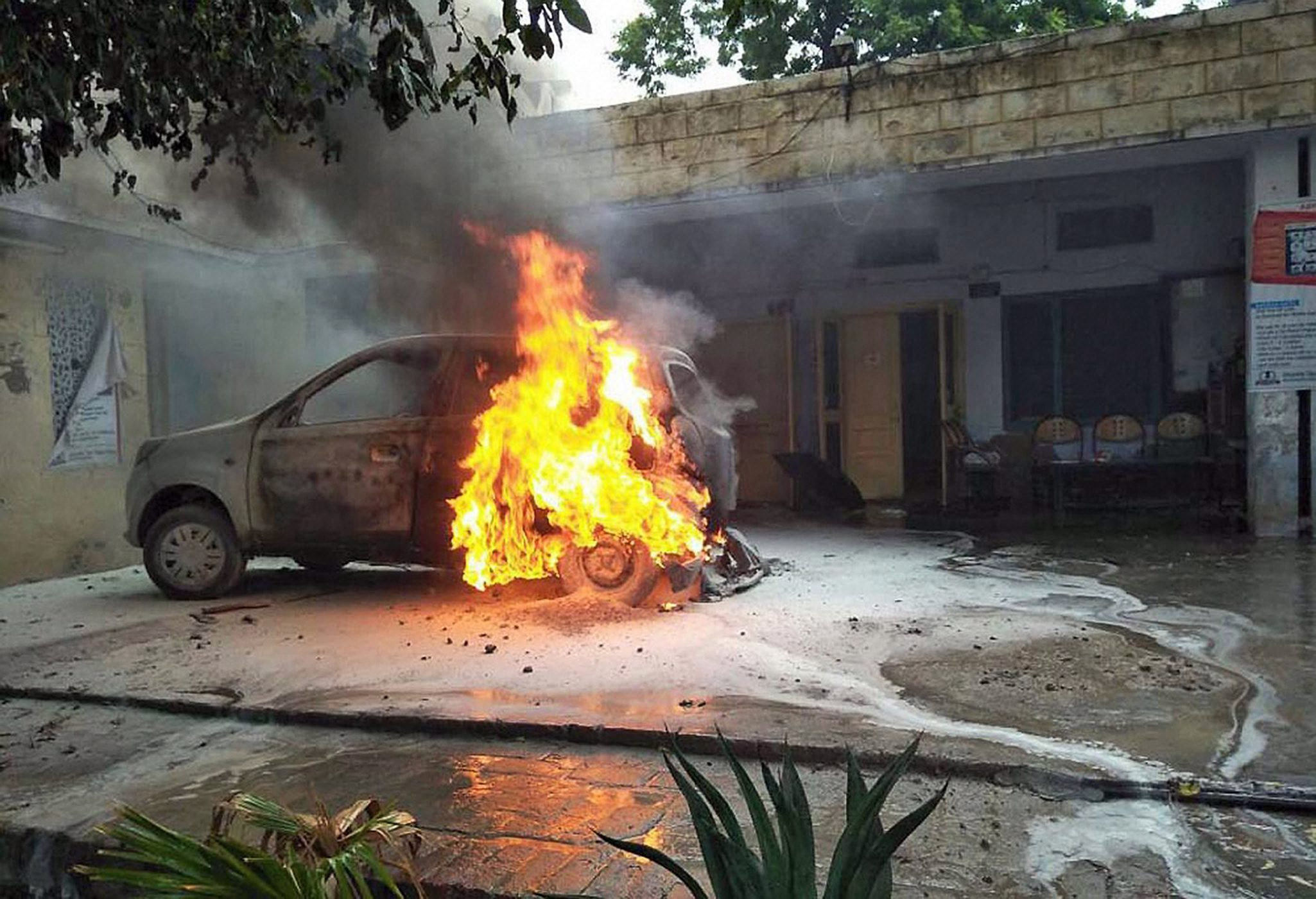 A car is set ablaze at an Income Tax office in Mansa, Punjab. (Credit: PTI)