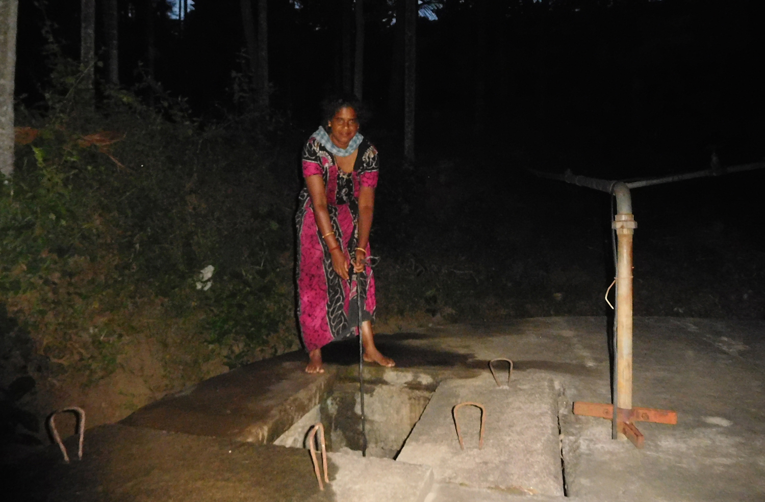 Bindu, a resident of Guddayoor, draws water from the public well at night.