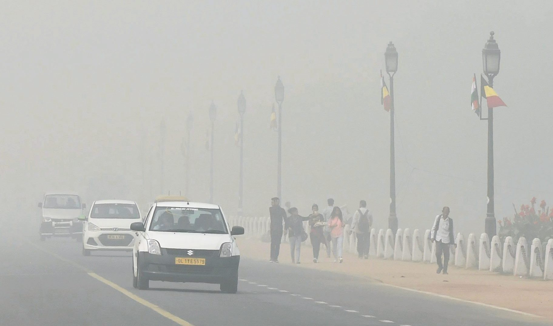Pedestrians and motorists make their way through thick smog in New Delhi on Tuesday (PTI)