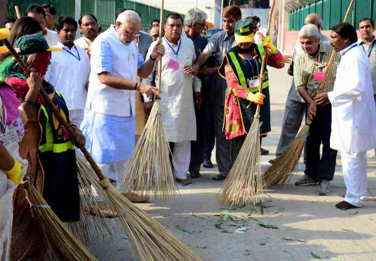 Prime Minister Narendra Modi sweeps a street in a residential colony in New Delhi on October 2, 2014. Photo: AFP