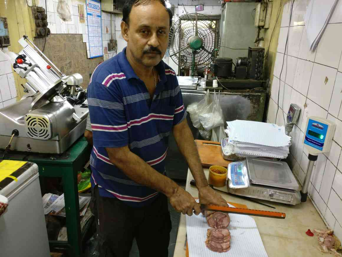 Joy Ghosh slices some cured ox tongue at Kalman