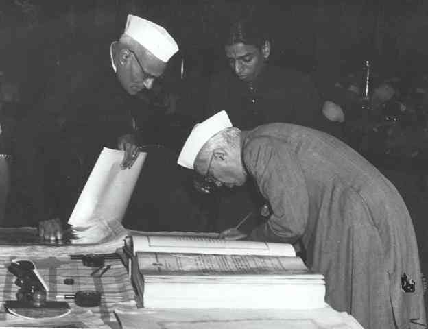 Jawaharlal Nehru signing the Indian Constitution, in 1950