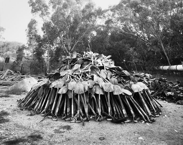 Lashing shovels retrieved from underground. Every grain of sand in the yellow tailings dumps that made the Witwatersrand landscape and every grain of gold that made its wealth, came from a rock off a black man's shovel underground. Central Salvage Yard, Randfontein Estates, Randfontein, 1966. David Goldblatt