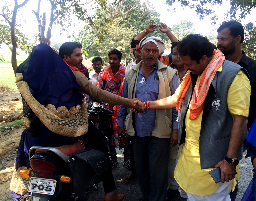 Satish Singh's supporters intercept a passing motorcyclist and make him shake hands with the candidate.