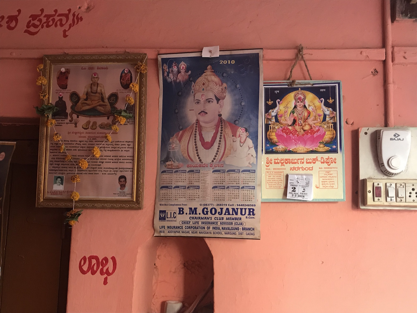 Basava, the 12th century social reformer, depicted on a wall calendar next to the Hindu goddess Laxmi at a Lingayat-owned shop in Gadag district.