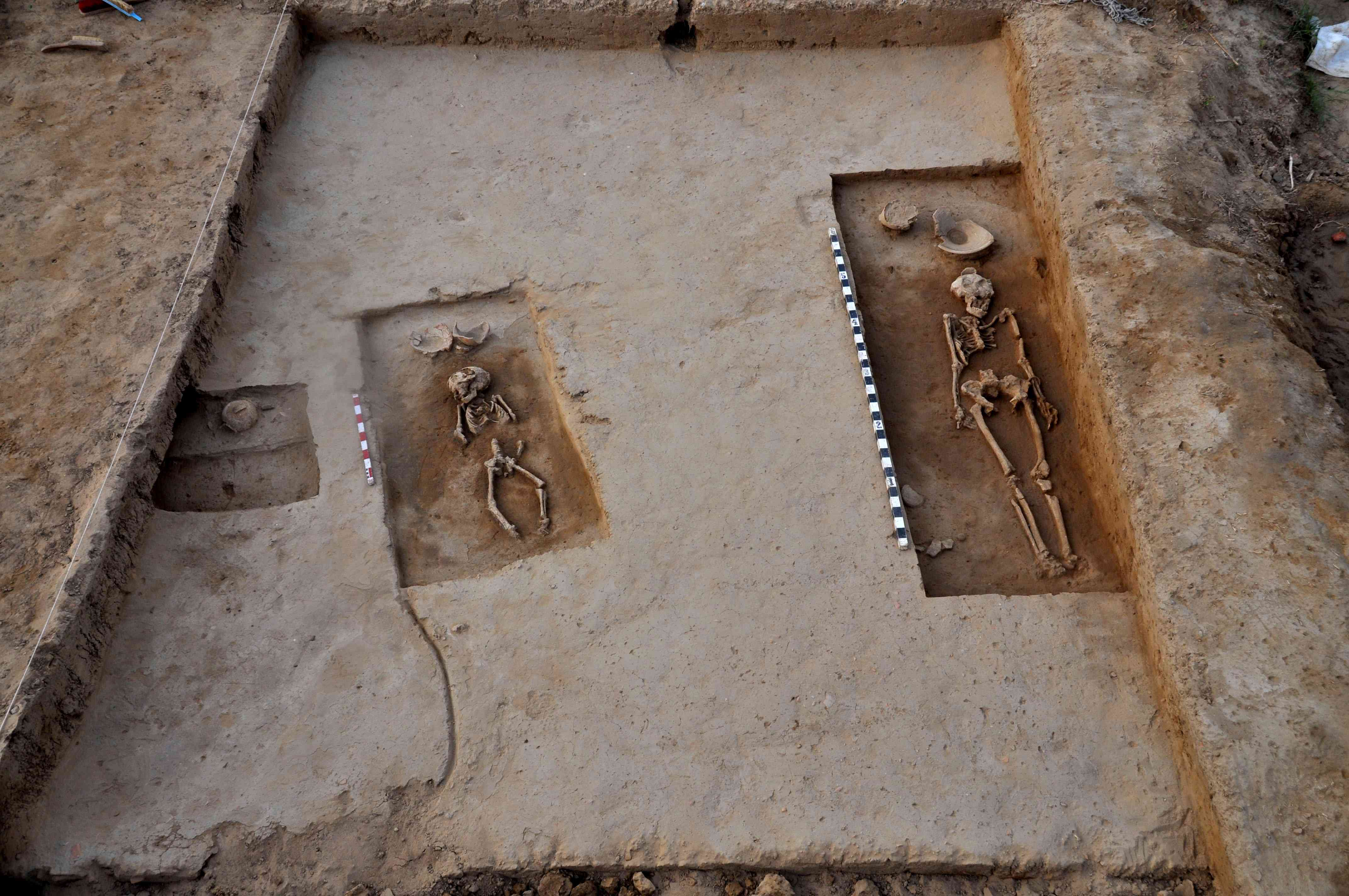 Two of four human skeletons dating back to the 5,000-year-old Harappan era, which have been recovered, are pictured at a burial mound at Rakhigarhi village in Hisar on March 11, 2015. Four complete human skeletons – two men, one woman and a child – were found. (Photo credit: Manoh Dhaka/AFP)