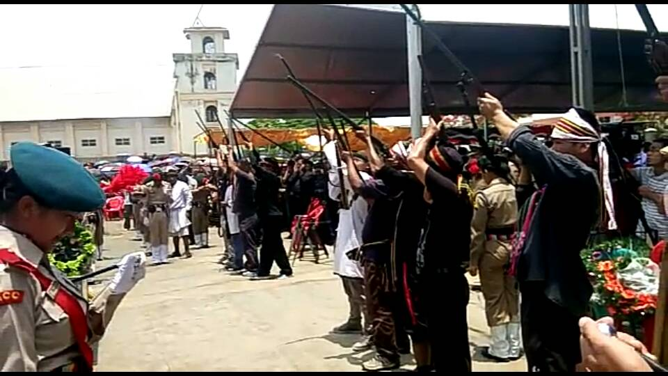 Local leaders pay homage to the dead with a gun salute at the public grounds.
