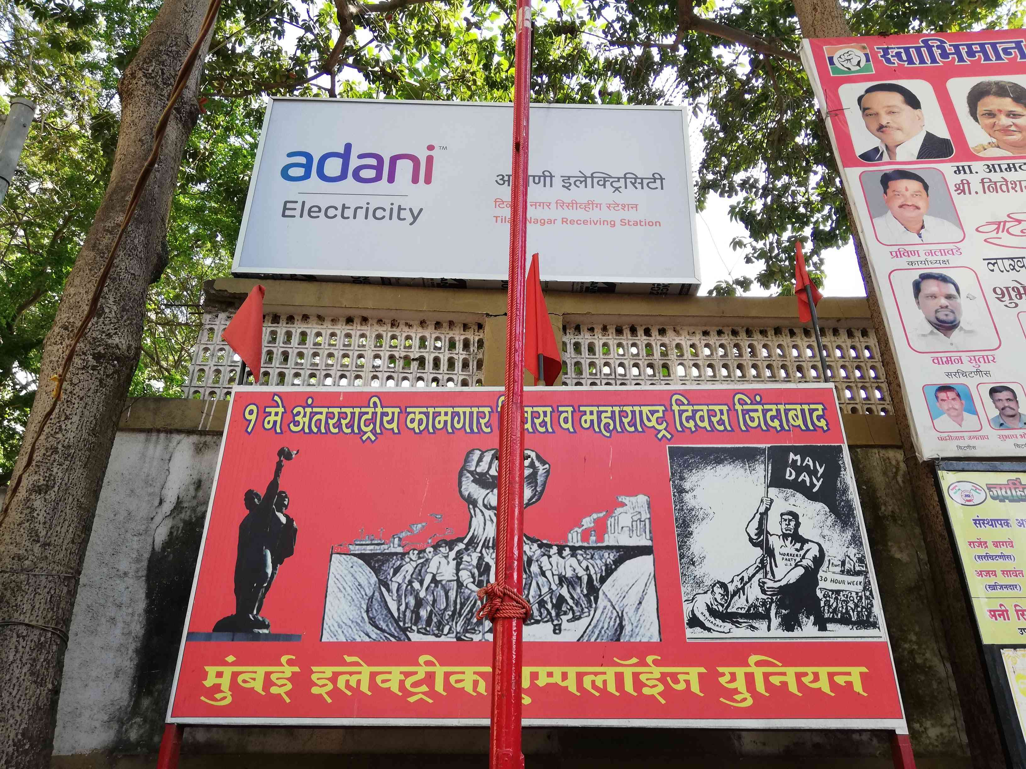A poster of the Mumbai Electric Employees Union behind a plain red flag hoisted in a concrete block outside the Tilak Nagar office of Adani Electricity Mumbai. Photo: Mridula Chari
