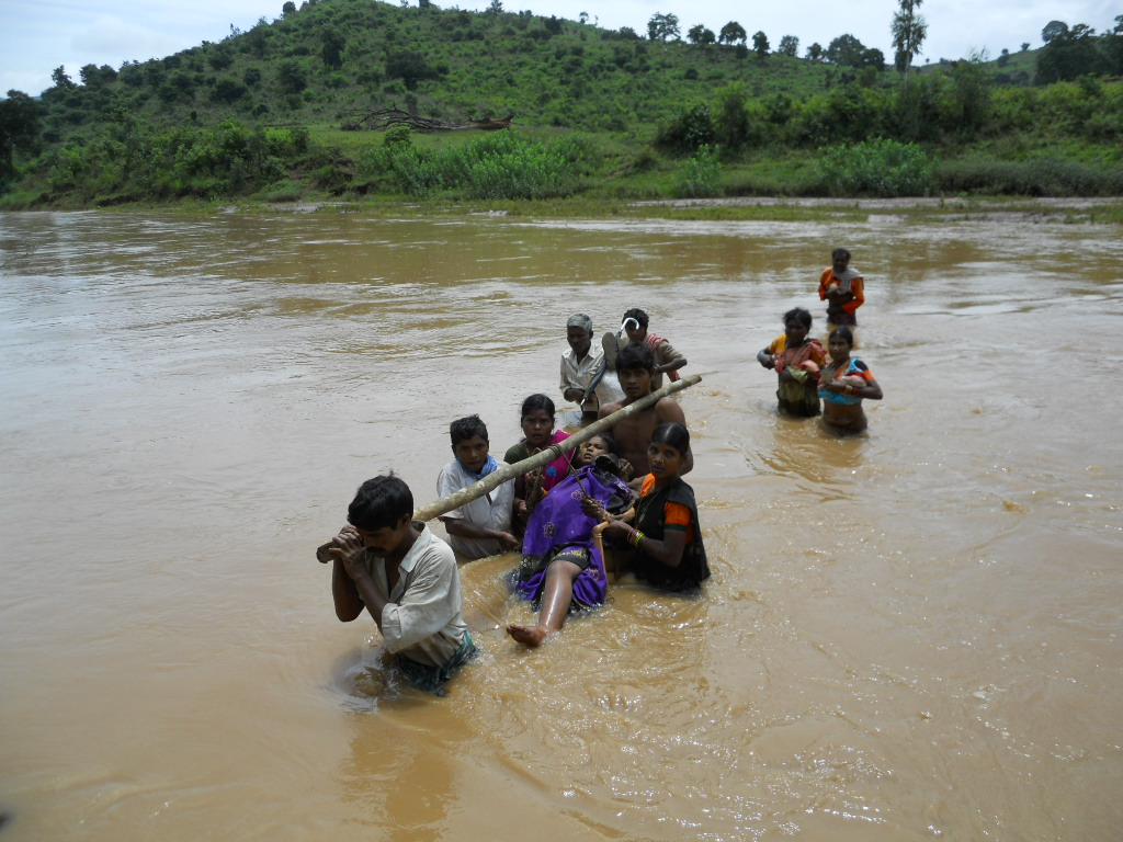 Eight months pregnant Santosini being carried across a river. Photo: Sarada Lahangir.