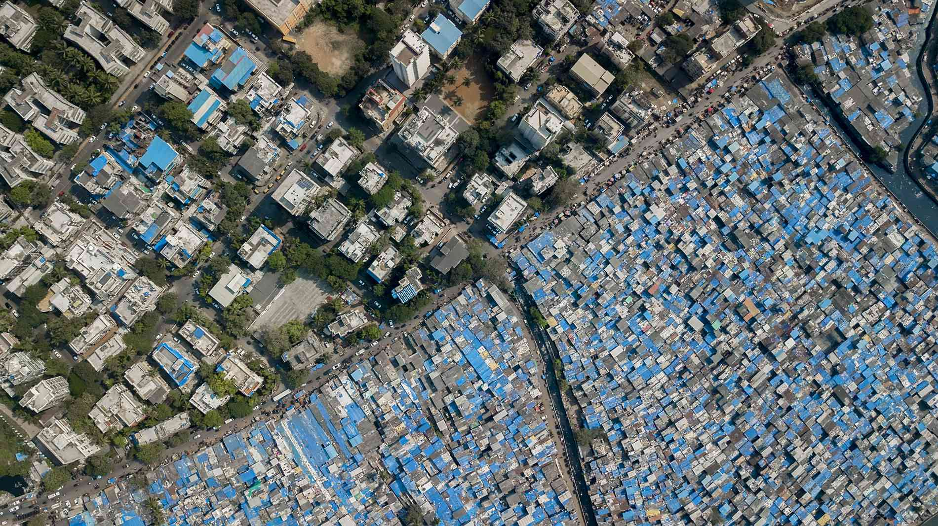 The contrast between Dharavi's tarpaulin covered shanties and the permanent structures beyond.