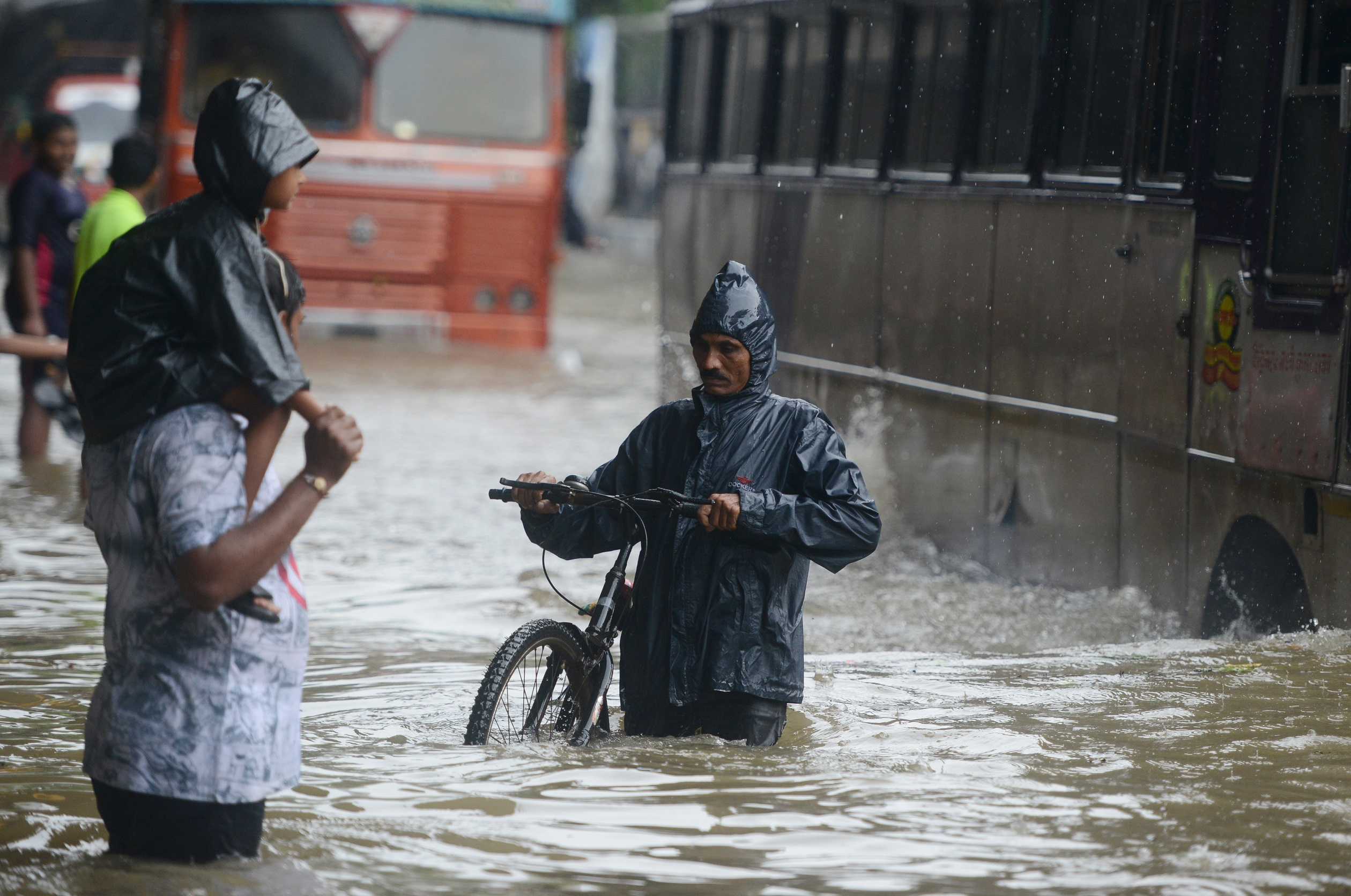 Vehicles and people struggle to wade through waterlogged streets in Mumbai on Tuesday. Credit: Punit Paranjpe/AFP