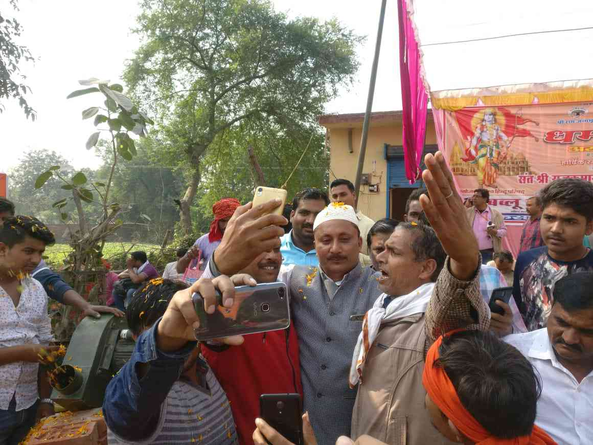 Babloo Khan, Ayodhya zila panchayat member from the BJP, clicks selfies with VHP workers coming in for the Dharma Sabha