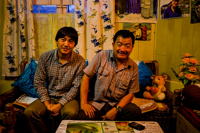 Kushang Sherpa, a trainer at the Himalayan Mountaineering Institute, holds a record for climbing Mount Everest from all five routes. Seated in his living room with his son, Kushang says he has lost several family members to mountaineering expeditions.