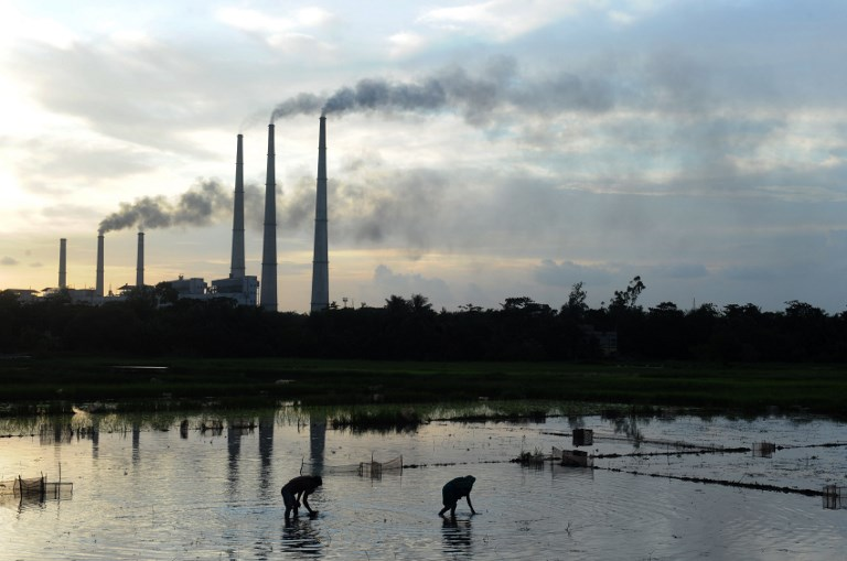 Labourers prepare the flooded field for rice farming as chimneys of Kolaghat Thermal Power Plant are seen in the background in Mecheda in West Bengal on July 26, 2011. [Photo: Dibyangshu Sarkar/AFP]