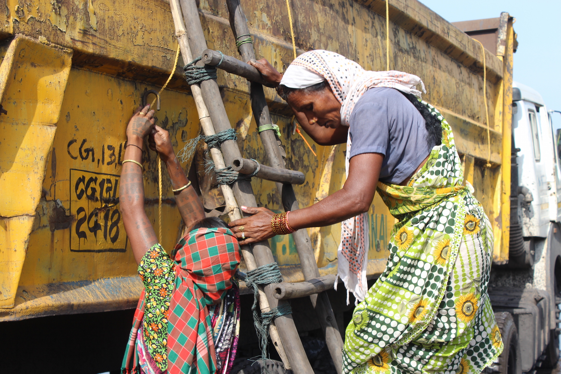 Description Gond Adivasi women climb up coal trucks to tie tarpaulin over them. This is the only work that is available to them, as women are yet to receive jobs in lieu of their land for Coal India's Chhal coal mine. September 2015. Photo credit: Aruna Chandrasekhar.