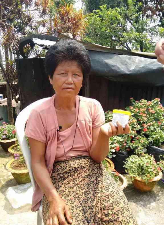 A Mizo woman sells a bottle of artisanal oil palm as massage oil.
