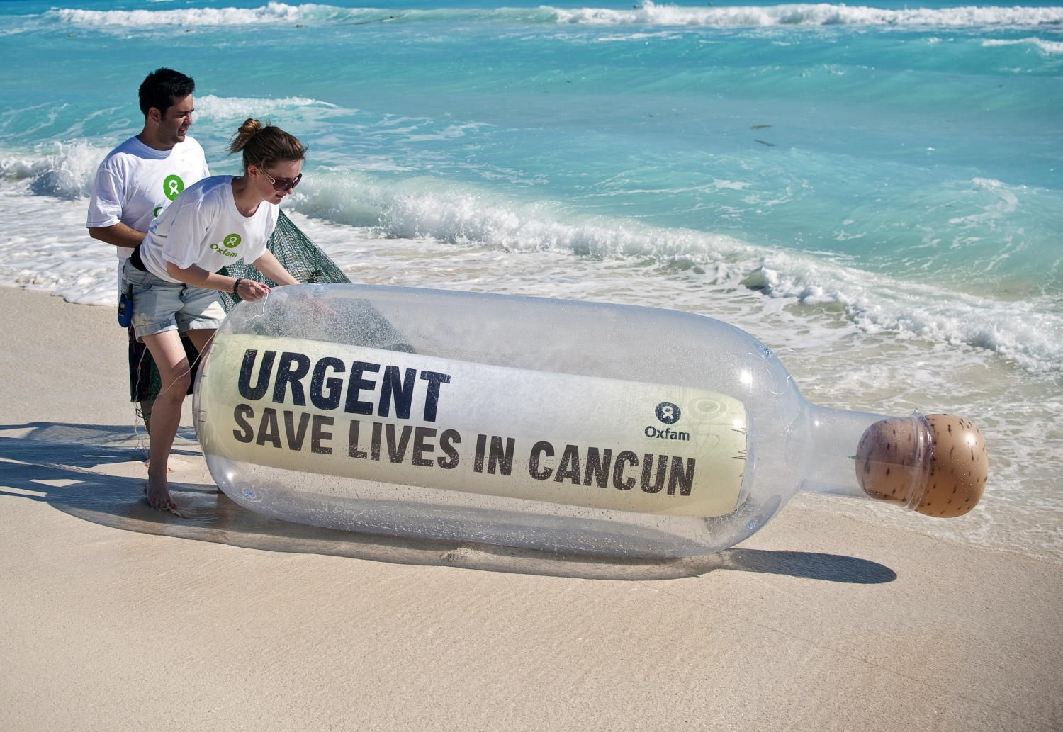 Oxfam activists place a bottle with a message in the beach during a demonstration, in Cancun, Mexico, ahead of the UN climate summit in 2010. (Photo credit: AFP).
